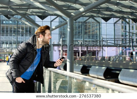Portrait of a cool guy standing with mobile phone at train station  - stock photo