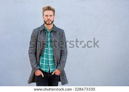 Portrait of a cool handsome man in jacket standing against gray background  - stock photo