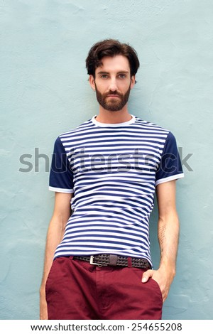 Portrait of a cool male model in striped shirt leaning against wall