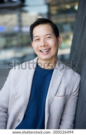 Portrait of a cool middle aged asian man smiling outdoors - stock photo