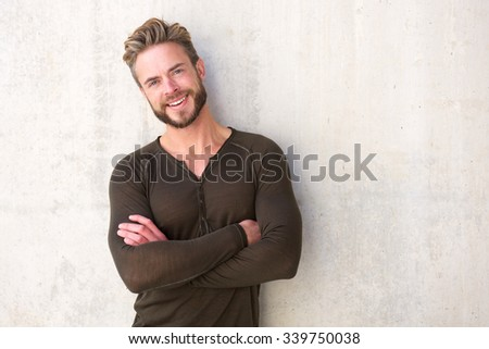Portrait of a cool modern man smiling with arms crossed - stock photo