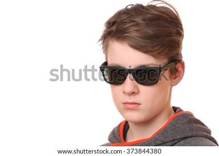 Portrait of a cool teenage boy wearing sunglasses on white background - stock photo