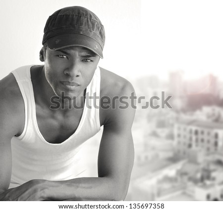 Portrait of a cool young man leaning on chair in white tank and trendy cap - stock photo