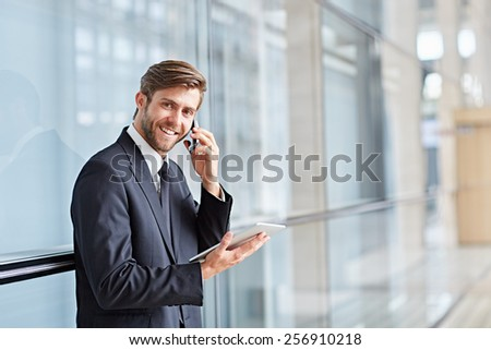 Portrait of a corporate executive smiling while talking on his phone and holding at a digital tablet - stock photo