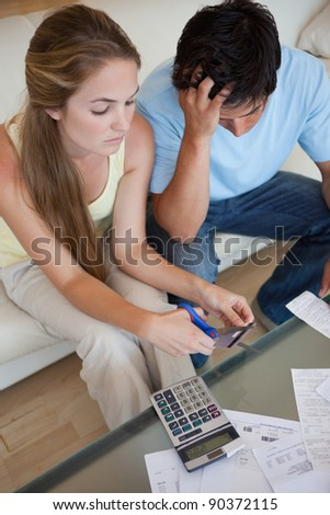 Portrait of a couple cutting their credit card in their living room - stock photo
