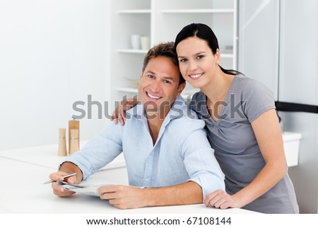 Portrait of a couple doing crossword together in the kitchen at home - stock photo