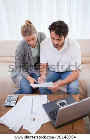 Portrait of a couple doing their accounting with a notebook in their living room