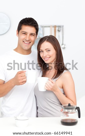 Portrait of a couple drinking coffee during breakfast standing in the kitchen - stock photo