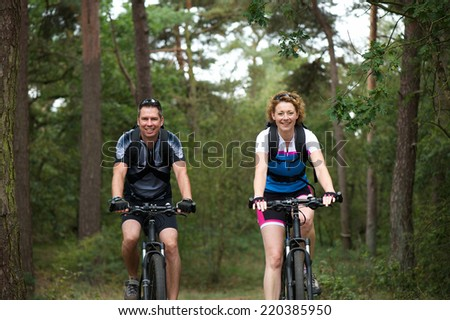 Portrait of a couple enjoying a bike ride in nature - stock photo