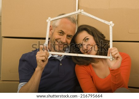 Portrait of a couple holding a scale in the shape of a house and smiling - stock photo