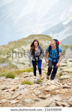 Portrait of a couple holding hands and talking on a mountain trail - stock photo