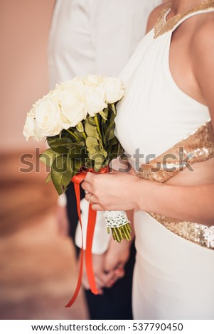 Portrait of a couple in love, hugs, bouquet of roses, white dress.