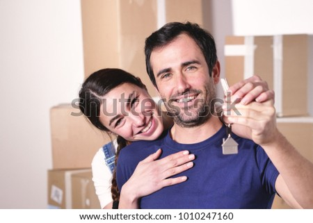 Portrait of a couple in love seated on the floor and they just bought a house and are moving. The bride and groom smile and hold the keys of the new house in their hands. Concept of: future, family.