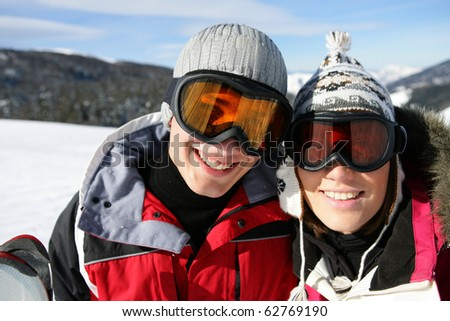 Portrait of a couple in snow wearing a mask of ski - stock photo