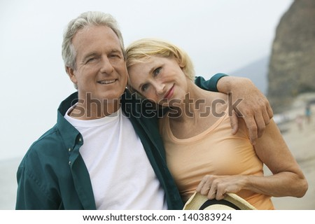 Portrait of a couple man with arm around a woman at the beach - stock photo