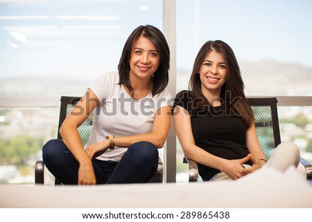 Portrait of a couple of female business partners looking cool and confident in an office with a view - stock photo
