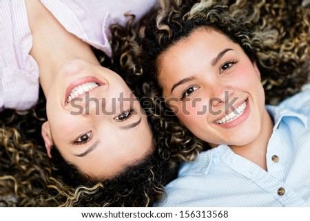 Portrait of a couple of happy twin sisters smiling  - stock photo