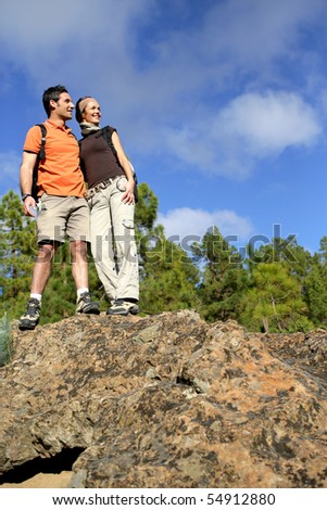 Portrait of a couple of hikers standing on a rock - stock photo