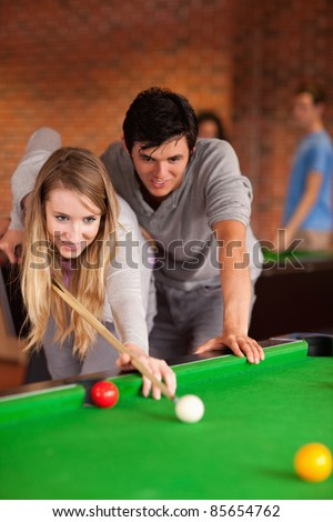 Portrait of a couple playing snooker in a student home - stock photo