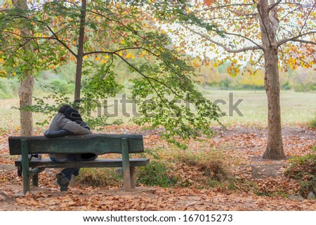 Portrait of a couple sitting on a bench in a park in autumn