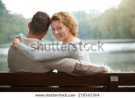 Portrait of a couple sitting on bench by a lake with woman smiling  - stock photo