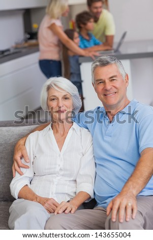 Portrait of a couple sitting on couch with their family in the kitchen behind them - stock photo