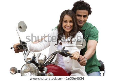 Portrait of a couple smiling while riding a motorcycle - stock photo