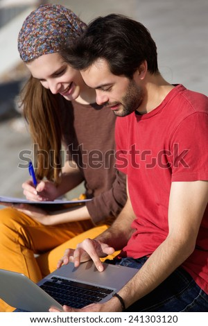 Portrait of a couple students working on laptop together outdoors - stock photo