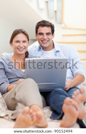 Portrait of a couple using a notebook while lying on a sofa in their living room - stock photo