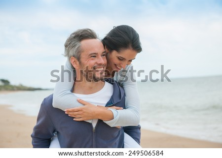 Portrait of a couple walking in the sand at the beach in casual clothes - stock photo