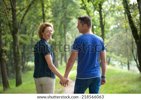 Portrait of a couple walking outdoors and holding hands