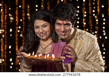Portrait of a couple with a tray of diyas - stock photo