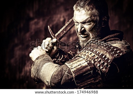 Portrait of a courageous ancient warrior in armor with sword. - stock photo