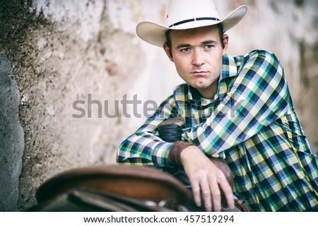 Portrait of a cowboy. He has a cowboy hat and he leans against a saddle - stock photo