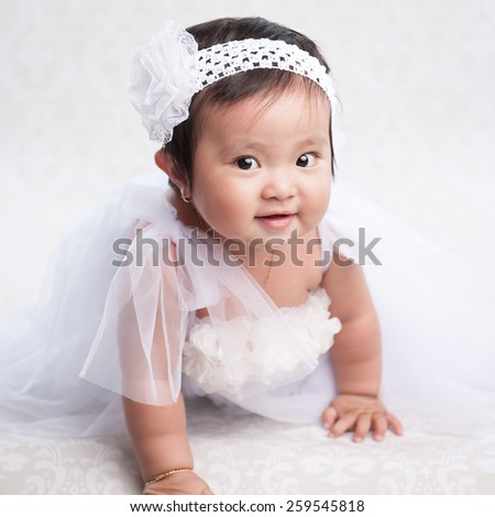 Portrait of a crawling baby on the bed in her room - stock photo