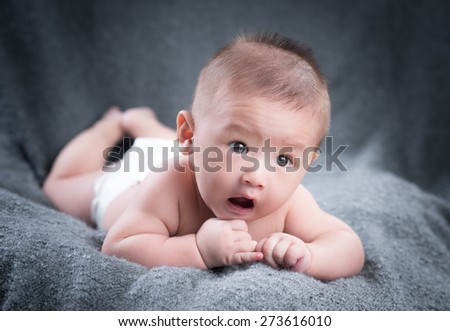 Portrait of a crawling baby on the bed in his room - stock photo