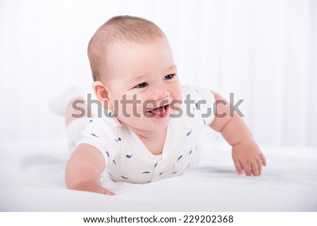 Portrait of a crawling baby on the carpet in the room. - stock photo