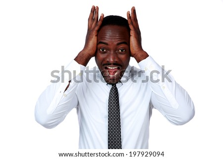 Portrait of a crazy african businessman shouting and closing ear by his hands on white background - stock photo