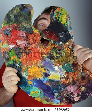 Portrait of a crazy artist plays with palette in hand - stock photo