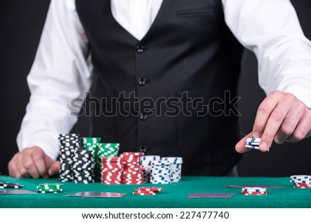 Portrait of a croupier is holding gambling chips on table. - stock photo