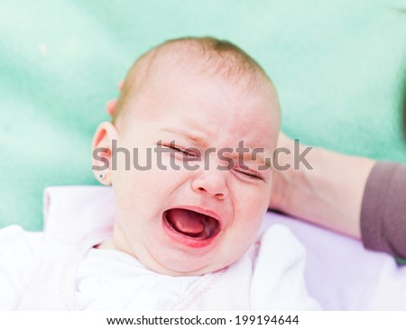 Portrait of a crying baby because she is teething