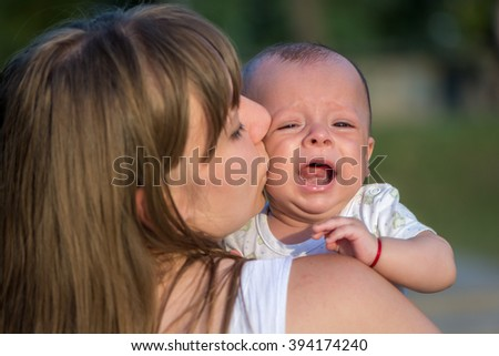 Portrait of a crying baby who is being held by her mother