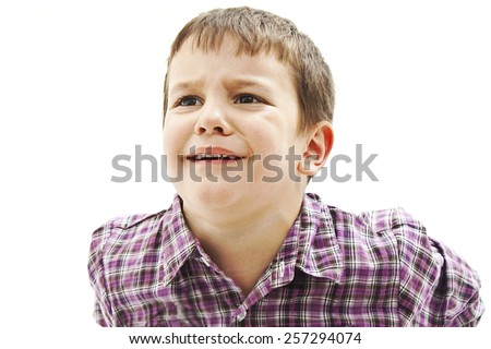 Portrait of a crying child, looking up. Isolated on white background  - stock photo