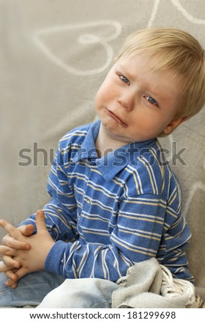 Portrait of a crying child with tears on his cheeks - stock photo