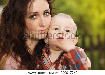 Portrait of a crying little boy who is being held by her mother, outdoors - stock photo