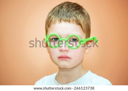Portrait of a crying little boy with glasses. - stock photo