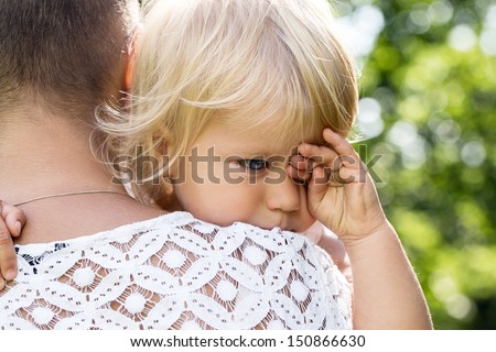 Portrait of a crying little girl who is being held by her mother - stock photo