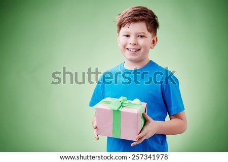 Portrait of a cure smiling boy holding a gift box - stock photo