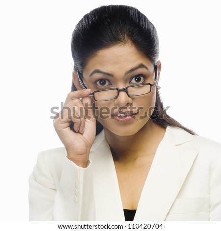 Portrait of a curious businesswoman holding her eyeglasses