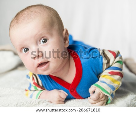 Portrait of a curious 2,5 months baby lying down on a blanket  - stock photo